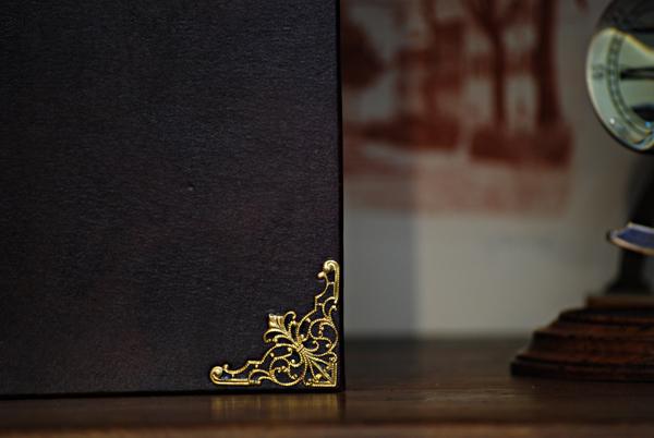 Quaderno con taglio sfrangiato in pelle con angoli metallici e giglio fiore