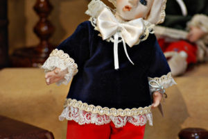 Pinocchio vestito con abiti di velluto blù e rosso con occhi di vetro