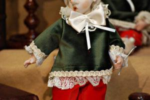 Pinocchio vestito con abiti di velluto verdi e occhi di vetro
