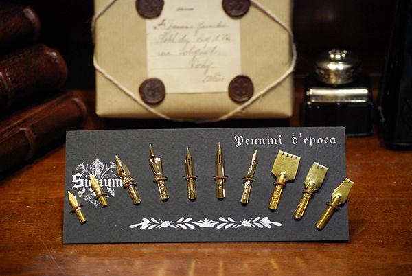 Cartella con dieci pregiati pennini dorati adatti a diverse scritture calligrafiche.