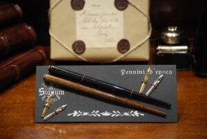 Cartella con due cannucce portapennini marrone scuro e nero e quattro pennini.