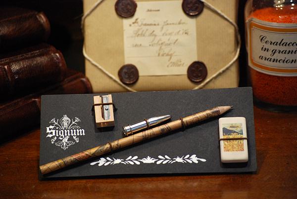 Cartella con un lapis in carta geografica, un salvapunta, un temperamatita e una gomma da cancellare raffigurante la Carta della Catena.