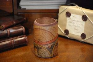 Barattolo in legno rivestito con carta geografica.