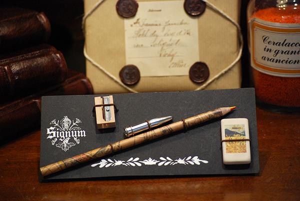 Cartella con una matita multicolore in carta geografica, un salvapunta, un temperamatita e una gomma da cancellare raffigurante la Carta della Catena.