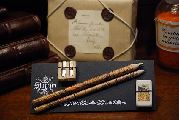 Cartella con un lapis e un matitone multicolore in carta geografica, un temperamatita e una gomma da cancellare raffigurante la Carta della Catena.